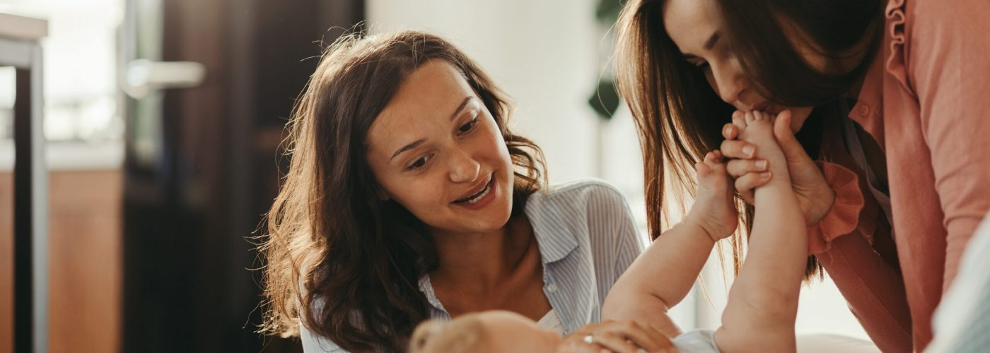 Two young women enjoying with a baby son while one of them is kissing his little foot.