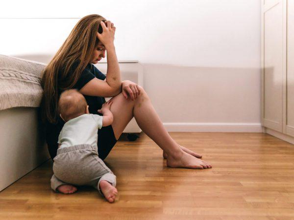 Erschöpfte Mutter auf dem Fußboden