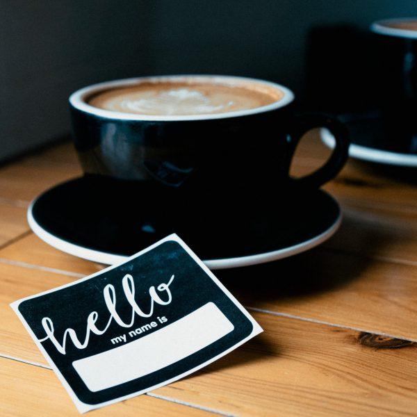 Tasse Kaffee mit Kärtchen daneben