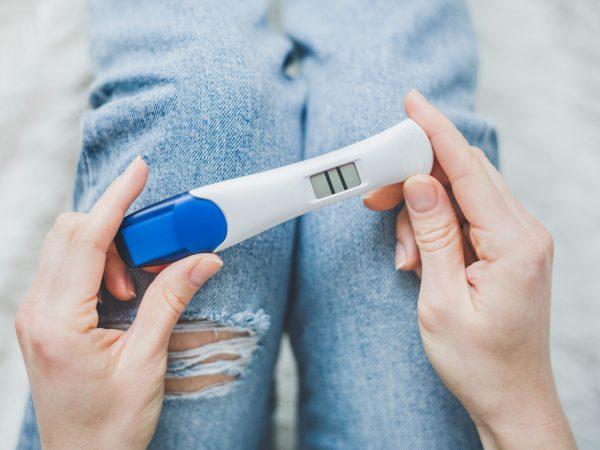 Hände mit positivem Schwangerschaftstest