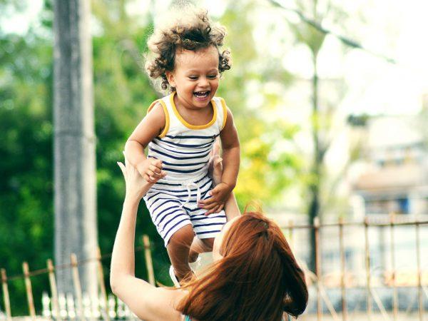 Mutter, die lachendes Kind in die Luft wirft