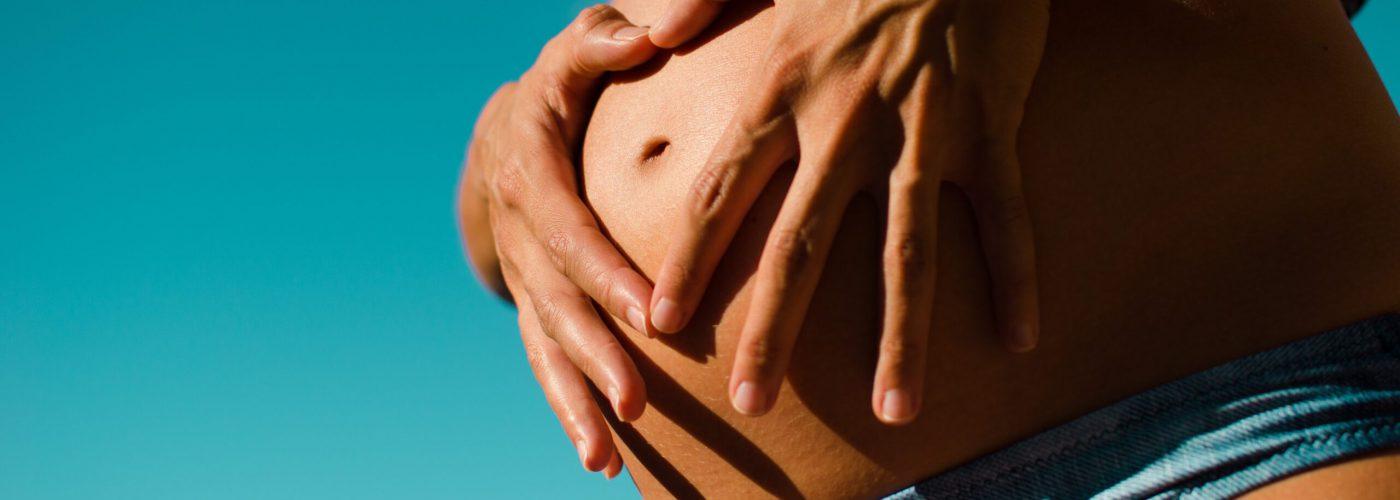 Frau formt mit Händen Herz vor ihrem Babybauch