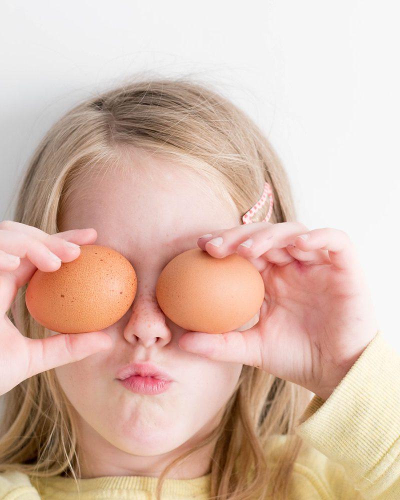 Kind hält sich Ostereier vor die Augen