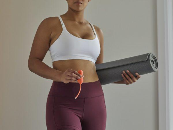 Frau mit Gymnastikmatte und Beckenbodentrainer
