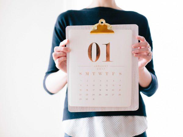 Frau hält Kalender in beiden Händen