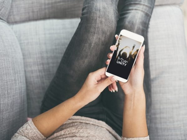 Frau mit Smartphone mit Momunity App in der Hand.
