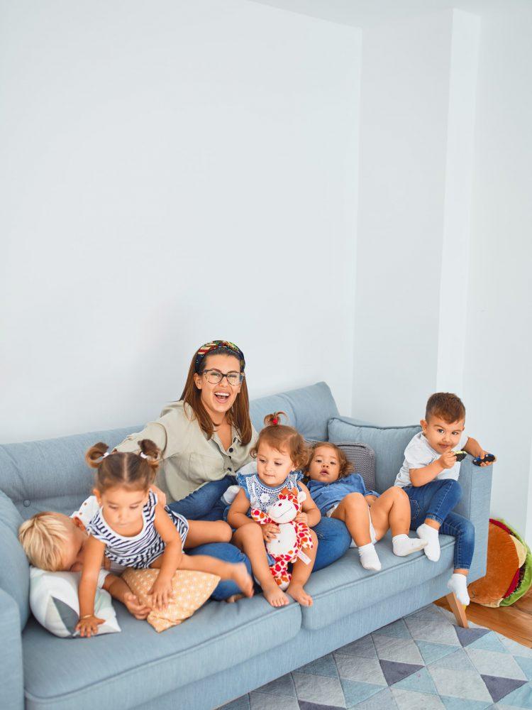 Tagesmutter mit Kindern auf dem Sofa